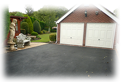 a photo of an asphalt driveway leading to a garage